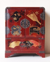 265.   Vintage japanese lacquer jewelry box with characteristic motifs on the top and round sideways.  :